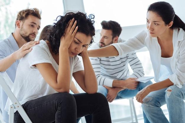 Freudlose unglückliche traurige frau, die ihren kopf hält und weint, während sie sich sehr verärgert fühlt