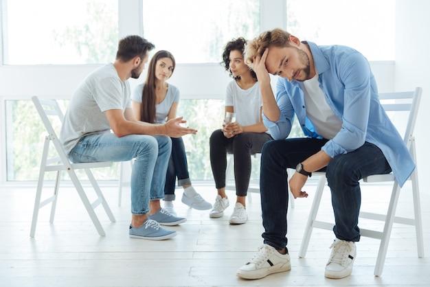 Freudloser düsterer junger mann, der seinen kopf hält und über seine probleme nachdenkt, während er sich unglücklich fühlt