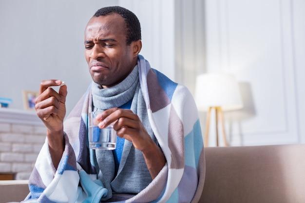 Freudloser unglücklicher launischer mann, der ein glas wasser hält und eine pille nimmt, während er zu hause sitzt