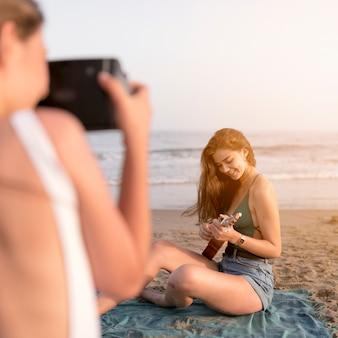 Freund, der das selfie des mädchens ukulele am strand spielend nimmt