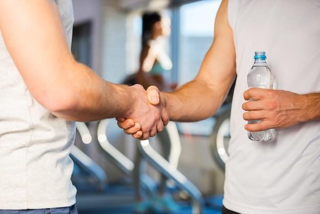 Freund im fitnessstudio treffen. zwei männer schütteln sich die hände, während sie im fitnessstudio stehen