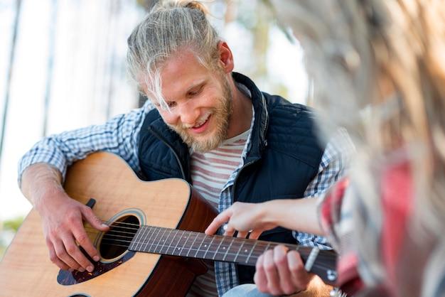 Freund spielt gitarre und frau berührt den griff