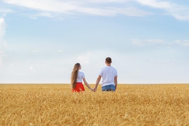Freund und freundin, die hände auf hintergrund des goldenen weizens und des blauen himmels halten