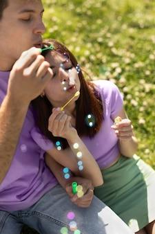 Freund und freundin spielen mit seifenblasen
