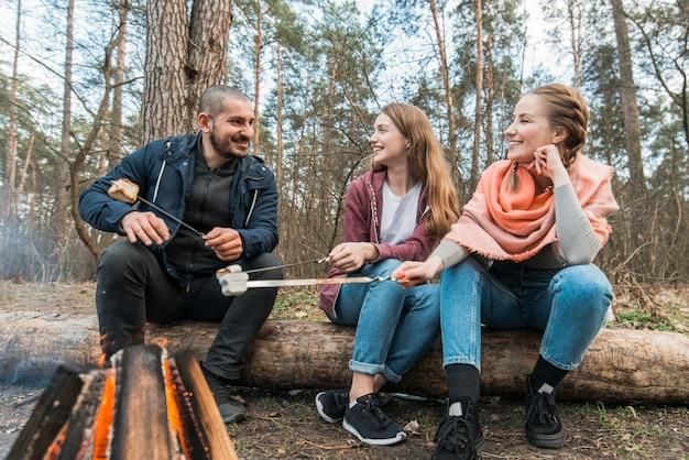 Freunde am lagerfeuer kochen marshmallow
