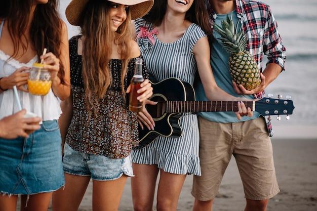 Freunde an einer strandparty mit gitarre