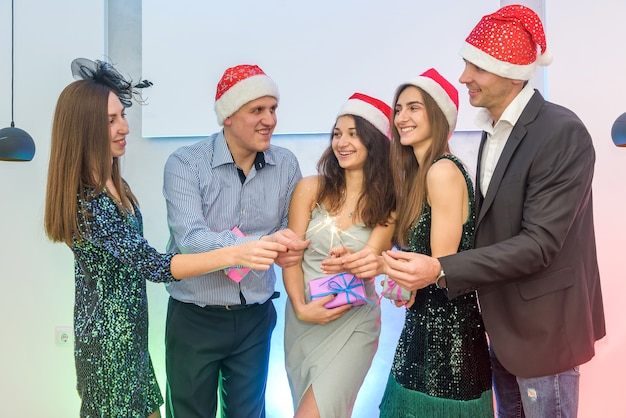 Freunde auf der neujahrsparty, die alle zusammen bengalische lichter zünden