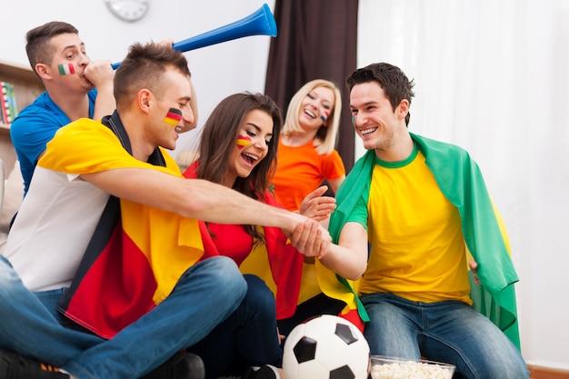 Freunde aus verschiedenen ländern unterstützen die fußballmannschaft