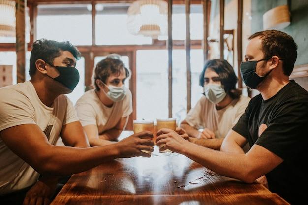Freunde beim biertrinken, maske im neuen normalen hd-bild
