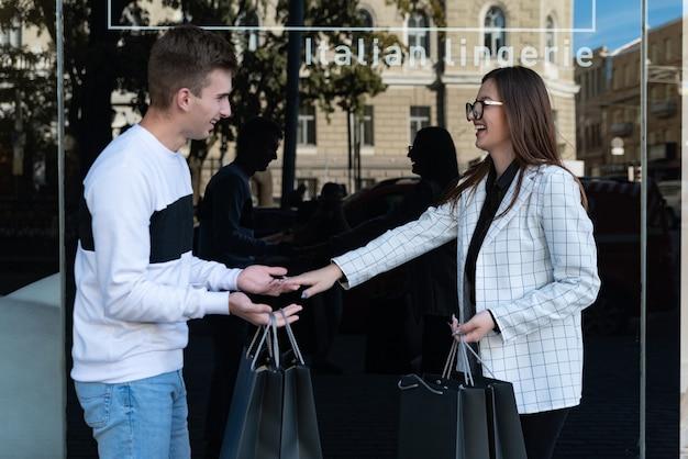 Freunde beim einkaufen. mädchen und ein kerl lachen vor dem hintergrund eines schaufensters. junger mann und frau mit einkaufstüten.