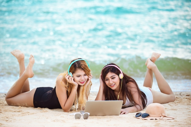 Freunde der jungen frauen hören musik auf dem strand, sommerkonzept.