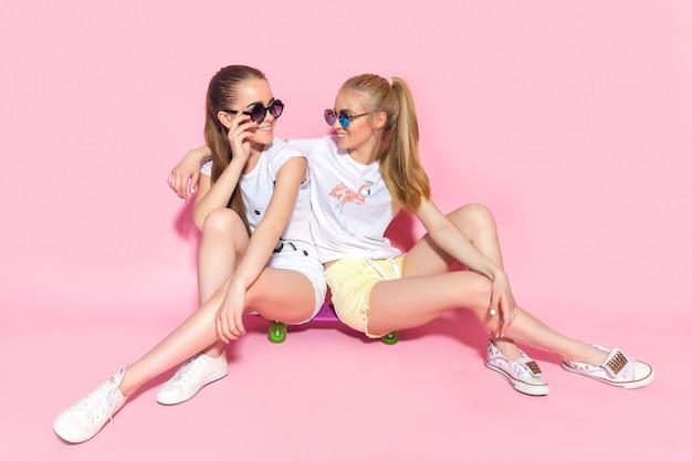 Freunde der jungen jugendlichen, die auf skateboard sitzen