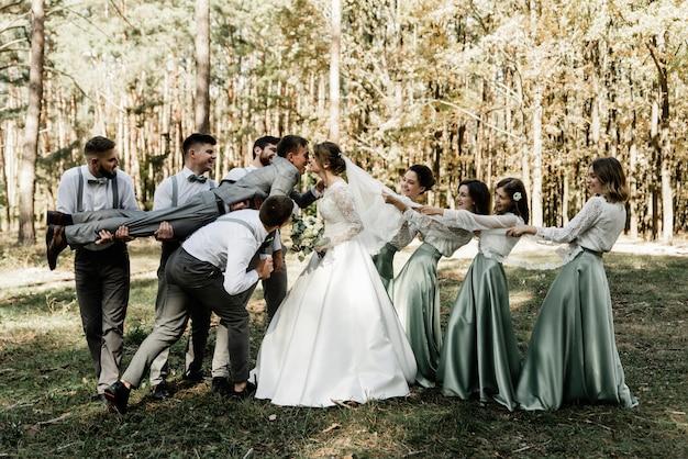 Freunde des bräutigams und brautjungfern halten das brautpaar in den armen