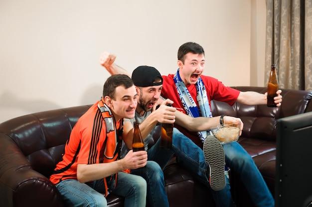 Freunde, die alkohol beim aufpassen des fußballs zujubeln und trinken