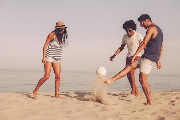 Freunde, die am strand spielen. drei fröhliche junge leute, die mit fußball am strand mit meer im hintergrund spielen