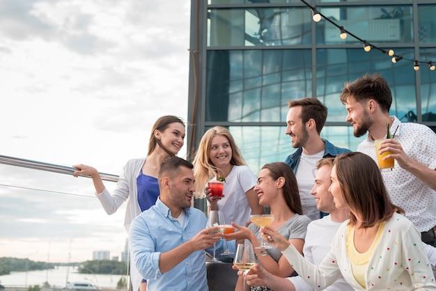 Freunde, die an einer terrassenparty rösten