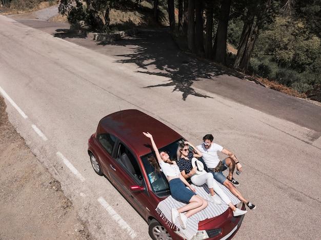 Freunde, die auf autohaube über der straße sich entspannen