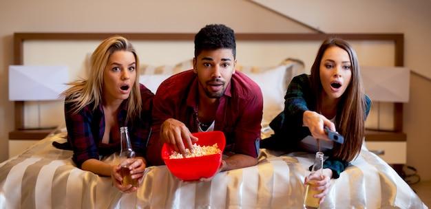 Freunde, die auf dem bett liegen, snacks und getränke haben und sich einen horrorfilm ansehen