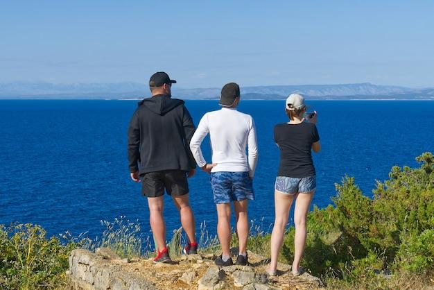 Freunde, die auf eine klippe über dem meer schauen, wanderer, die die aussicht betrachten und sommerabendaktivitäten genießen