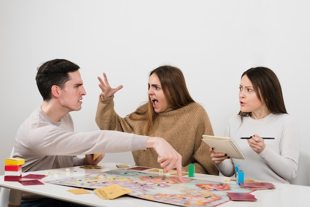 Freunde, die auf einem brettspiel argumentieren