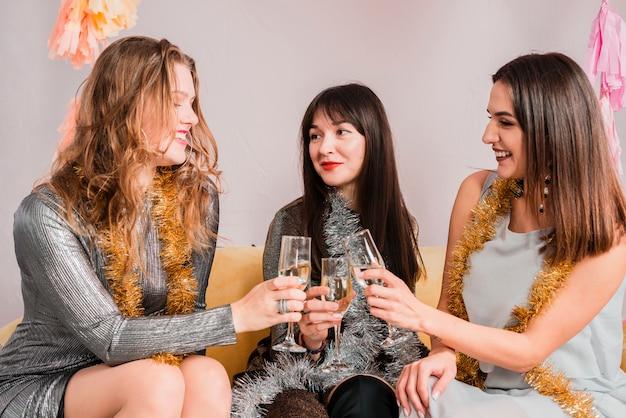 Freunde, die auf einem sofa an einer party des neuen jahres plaudern