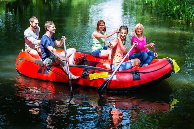 Freunde, die auf gummiboot am waldfluß oder am nebenfluss schaufeln