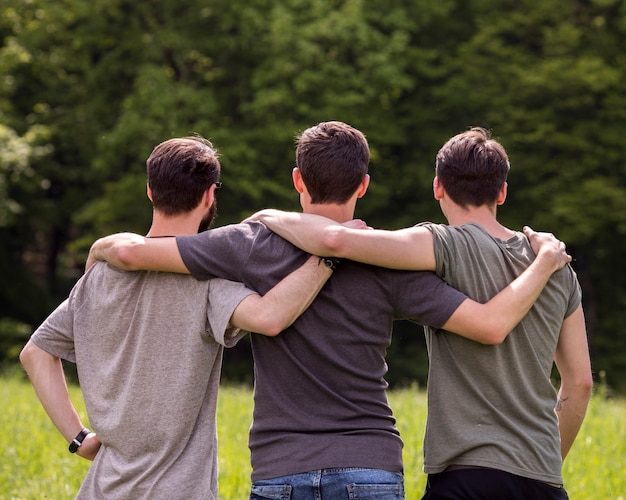 Freunde, die auf lichtung mit den händen auf einander schultern stehen