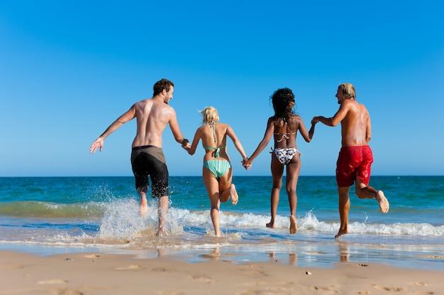 Freunde, die auf strandferien laufen
