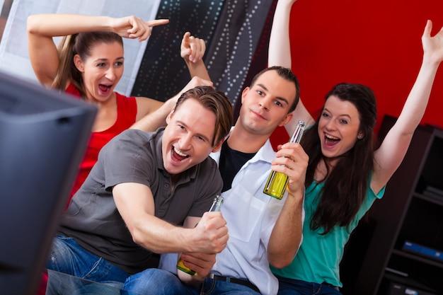 Freunde, die aufregendes spiel am fernsehen aufpassen