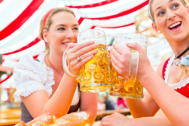 Freunde, die bayerisches bier am oktoberfest trinken
