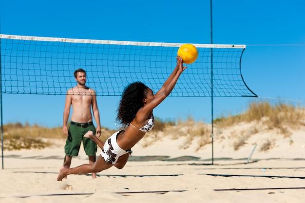 Freunde, die beachvolleyball spielen