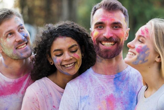 Freunde, die bedeckt in der pulverisierten farbe lächeln und aufwerfen