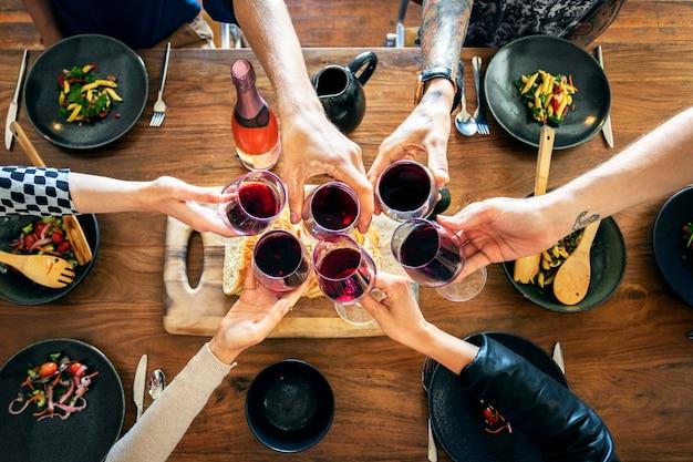 Freunde, die bei einer dinnerparty anstoßen