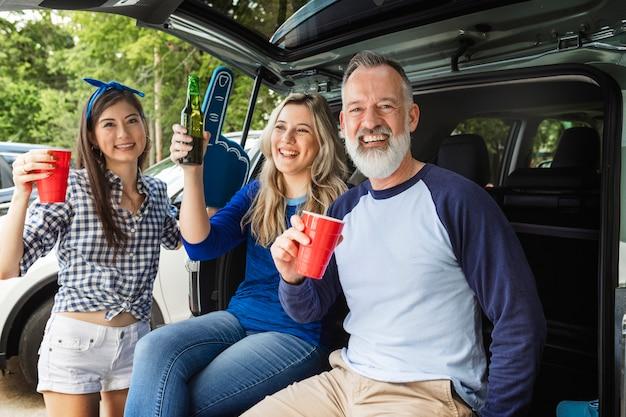 Freunde, die bei einer heckklappenparty im kofferraum sitzen und trinken