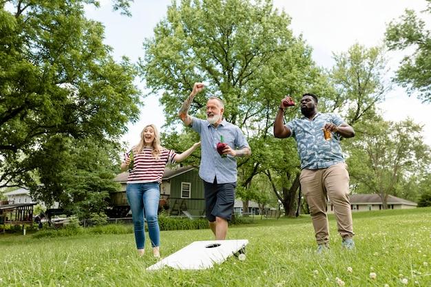 Freunde, die bei einer sommerparty im park cornhole spielen