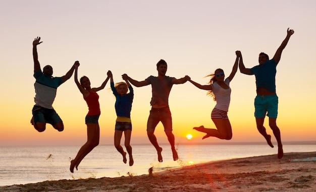Freunde, die bei sonnenuntergang am strand am meer springen