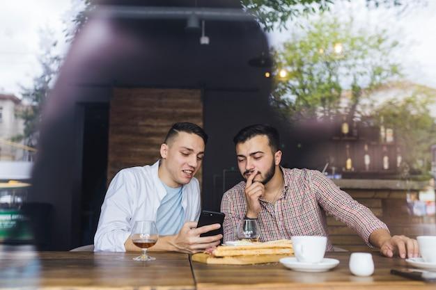 Freunde, die bei tisch im restaurant gesehen vom fensterglas sitzen