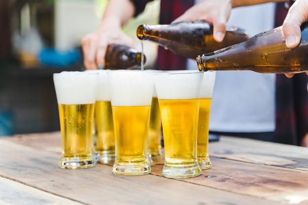 Freunde, die beim camping im freien eine flasche bier klirren