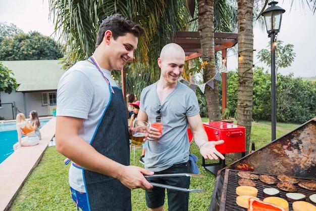 Freunde, die beim grillen kochen