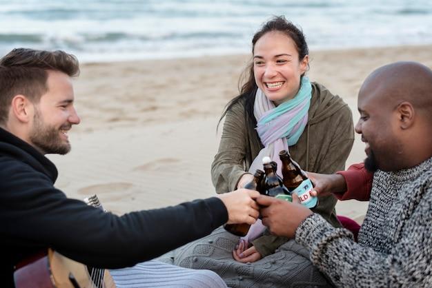 Freunde, die bier am strand trinken