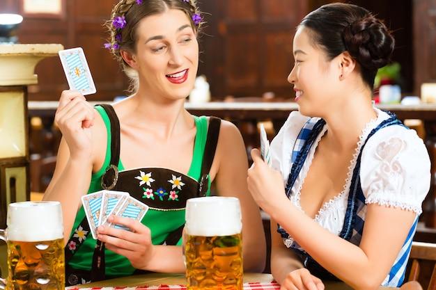 Freunde, die bier in den spielkarten des bayerischen pubs trinken