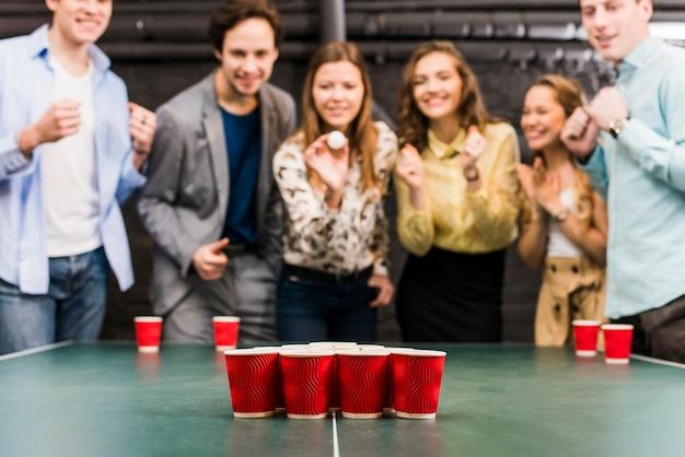 Freunde, die bier pong spiel auf tabelle in der bar genießen
