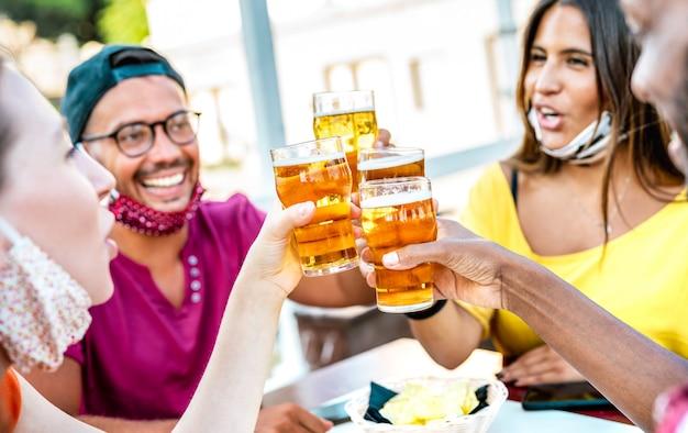 Freunde, die biergläser mit gesichtsmasken rösten - niederländische winkelkomposition mit selektivem fokus auf gläsern