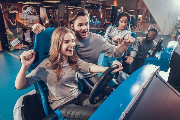 Freunde, die blaue autos in der spielhalle reiten ein team gewinnt
