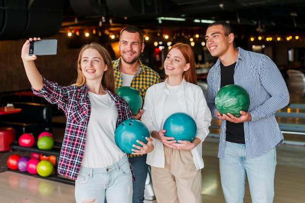 Freunde, die bunte bowlingspielkugeln anhalten