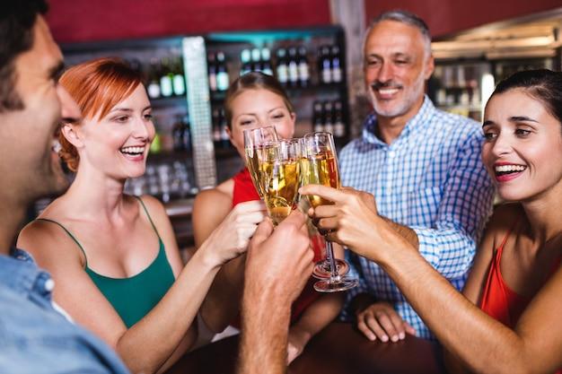 Freunde, die champagnerglas im nachtklub rösten