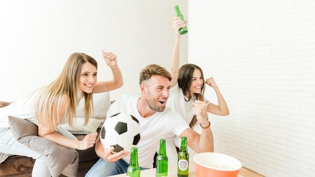 Freunde, die das ziel sitzt an der couch feiern