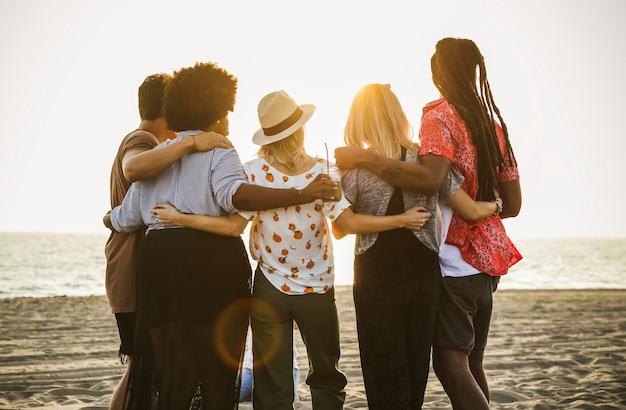 Freunde, die den sonnenuntergang am strand aufpassen