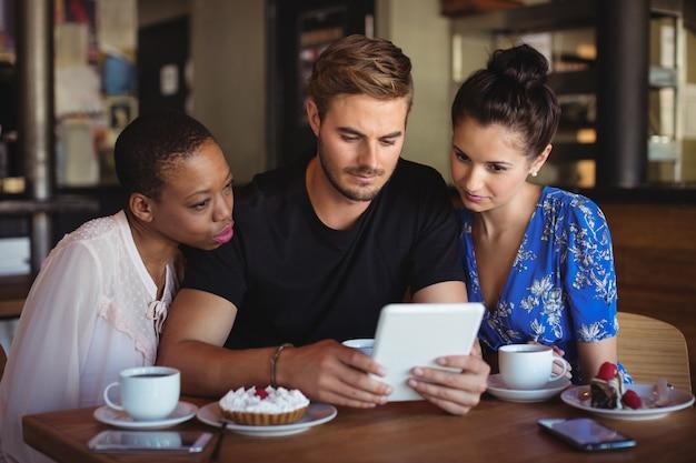 Freunde, die digitales tablet beim frühstück verwenden