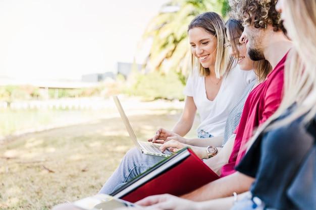 Freunde, die draußen mit laptop studieren